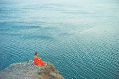 Woman in red dress looking at sea. Outdoor lifestyle photo of woman in red dress looking at sea. Travel background. Tourism Royalty Free Stock Photography