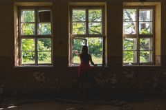 Woman in red dress looking through the window Stock Images