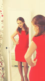 Woman in a red dress looks in the mirror Stock Photos