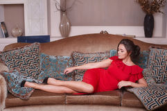 Woman in red dress lying on the sofa in the living room Royalty Free Stock Image
