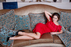 Woman in red dress lying on the sofa in the living room Stock Image