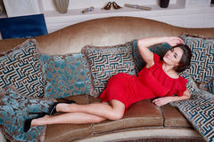 Woman in red dress lying on the sofa in the living room Stock Photography