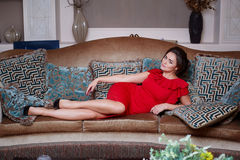 Woman in red dress lying on the sofa in the living room Royalty Free Stock Photos