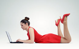 Woman in red dress lying and working with a laptop Stock Image