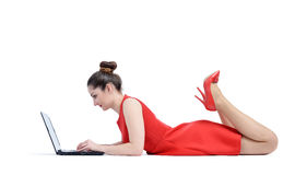 Woman in red dress lying and working with a laptop, on white background Royalty Free Stock Image
