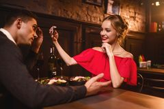 Woman in red dress makes image of her man on phone Stock Images