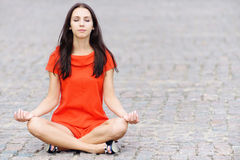 Woman in red dress meditates Royalty Free Stock Images