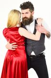 Woman in red dress and man in vest cuddling while dancing. Bearded hipster and attractive lady at dancing contest. Woman in red dress and men in vest cuddling Stock Images