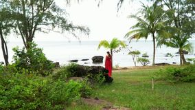 Woman in a red dress on the ocean coast. Tropics of Vietnam. Island of Phu Quoc.  stock video