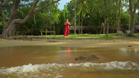 Woman in a red dress on the ocean coast. In the tropics of Vietnam. Island of Phu Quoc stock video