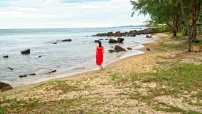 Woman in a red dress on the ocean coast. Tropics of Vietnam. Island of Phu Quoc.  stock video footage