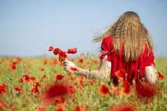 Woman at red dress with poppies bouquet Stock Photography