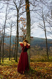 Woman in red dress portrait, autumnal forest Royalty Free Stock Photos