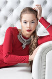 Woman in red dress. Portrait of beautiful young woman with stylish make up, elegant jewelry and in red dress looking at the camera Stock Photos