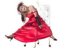 Woman in a red dress posing on a chair Royalty Free Stock Photography