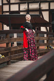 Woman in red dress posing on wooden bridge at old european city Stock Images