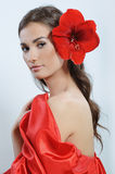 Woman in red dress with a red lily in her hair Stock Photo