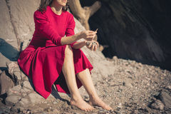 Woman in red dress relaxing by cave on beach Stock Images