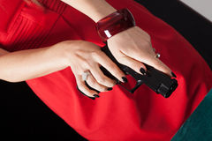 Woman in red dress reloading pistol Royalty Free Stock Photography
