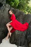 Woman in red dress on the rock Royalty Free Stock Photo