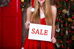 Woman in red dress with sale sign over christmas Stock Photos