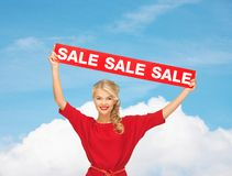 Woman in red dress with sale sign Stock Image