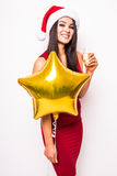 Woman in red dress and santa christmas hat with gold star shaped balloon smiling and drinking champagne Royalty Free Stock Images