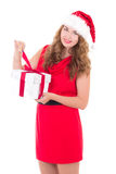 Woman in red dress and santa hat with christmas present isolated Royalty Free Stock Images