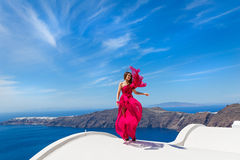 Woman in the red dress and sea. Woman in the red dress looks at the sea from the high roof Stock Image