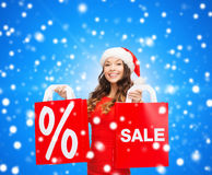 Woman in red dress with shopping bags. Sale, gifts, christmas, holidays and people concept - smiling woman in red dress with shopping bags and percent sign on Royalty Free Stock Images