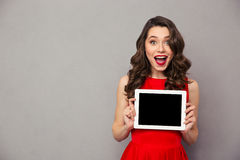 Woman in red dress showig blank tablet computer screen. Portrait of a cheerful woman in red dress showig blank tablet computer screen over gray background Stock Image