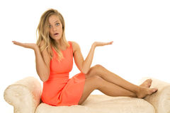 Woman in red dress sit on white sofa hands up Royalty Free Stock Photo
