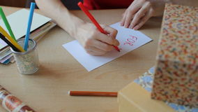 Woman in red dress sits at the wooden table, takes a red felt pen and makes greeting card stock video footage