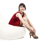 Woman in red dress sitting on armchair. Relaxing smiling Stock Images