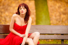 Woman red dress sitting on bench in autumn park Stock Photography