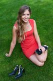 Woman in red dress sitting on green grass Stock Photography