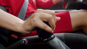 Woman in red dress sitting inside of vehicle and checks the gearbox in a car before driving. Close up of woman in red dress sitting inside of vehicle and stock video footage
