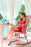 Woman in red dress sitting at light cafe Stock Photography