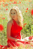 Woman in red dress sitting among poppy field Royalty Free Stock Photo