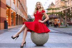 Woman in red dress sitting on the sphere Royalty Free Stock Images