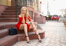 Woman in red dress sitting on the stairs. Beautiful blonde woman in red dress and high heels sitting outdoor on the stone stairs outdoor Royalty Free Stock Photo