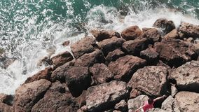 Woman in red dress standing on the rocky cliff with hands apart with blue water hitting against rocky pier beach. Aerial view of s. Ea waves colliding with rocks stock footage