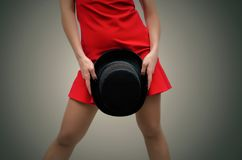 Woman with bowler hat. Woman in red dress and stockings is holding in hands a black bowler hat in front of herself on dark background stock images