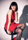 Woman in red dress and stockings sitting on bar chair Stock Photo