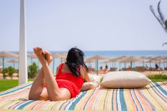 Woman in red dress on sun holidays at Red Sea Stock Image