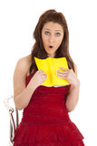 Woman red dress surprised at book Stock Image