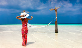 Woman in red dress takes a photo of a beach setting in the Maldives. Elegant woman in red dress takes a photo of a beach setting in the Maldives Royalty Free Stock Photos