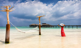 Woman in red dress takes photos in a Maldivian beach setting Stock Photo