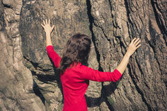Woman in red dress touching rock wall Stock Photo