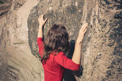 Woman in red dress touching rock wall Royalty Free Stock Image